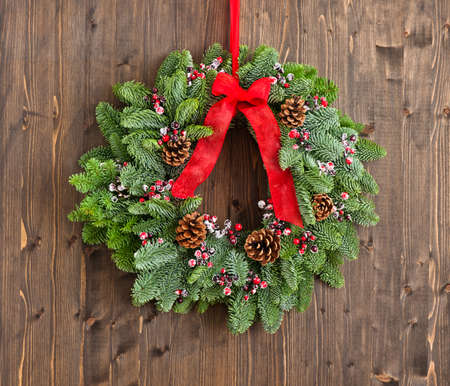 Advent wreath with red ribbon over wooden wall Standard-Bild