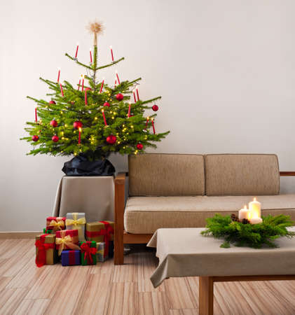 Christmas tree decorated with presents in living room photo