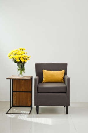 Grey sofa armchair in simple setting with yellow flowers photo
