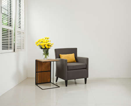 interior designer: Grey sofa armchair in simple setting infront of lovered windows Stock Photo
