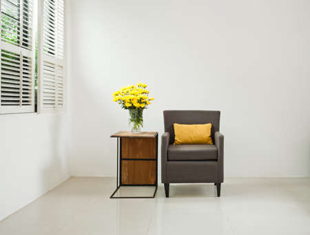 Grey sofa armchair in simple setting infront of lovered windows photo