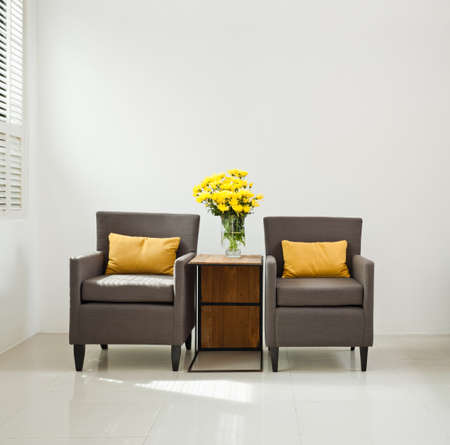 Grey sofa armchair in simple setting with yellow flowers Stock Photo