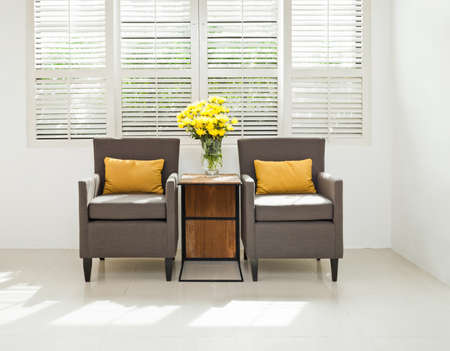 louvered: Grey sofa armchair in simple setting infront of lovered windows Stock Photo