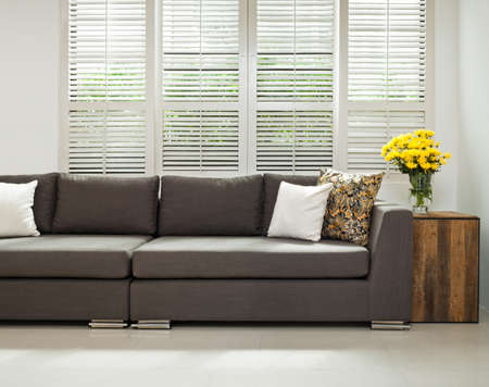 wood blinds: Grey sofa with pillows infront of lovered windows