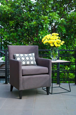 garden furniture: Outdoor patio seating with single chair in the evening Stock Photo