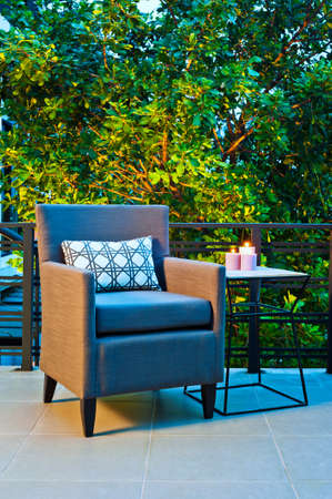 modern garden: Outdoor patio seating with single chair in the evening Stock Photo