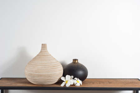 Empty vases decorated with Frangipani flower over side board