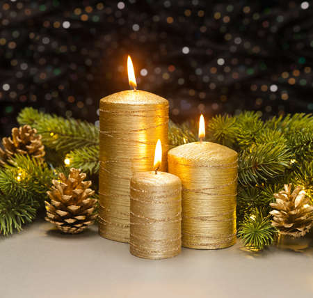 pine three: Three golden Candles with Christmas tree branches and pine cones decorated