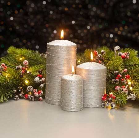Three Silver Candles with Christmas tree branches and red berries decorated photo