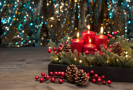 corona de adviento: Tres velas rojas con ramas de árboles de Navidad y conos de pino decorados Foto de archivo