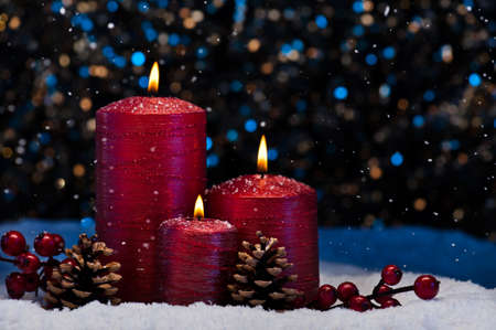 Three Red Candles in snow with snowfall photo
