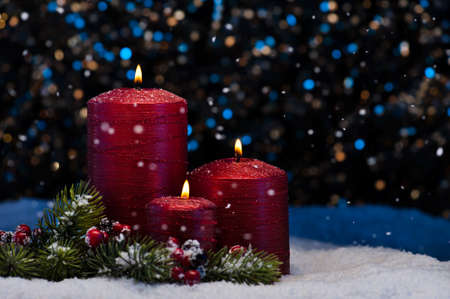 Three Red Candles in snow with snowfall