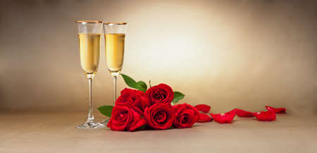 Champagne glasses, present and roses in front of beige background photo