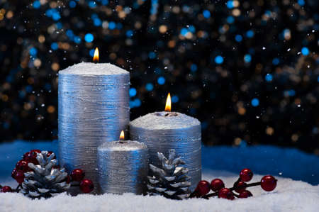 pine three: Three Silver Candles in snow with snowfall Stock Photo