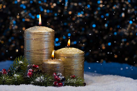 lit candle: Three Golden Candles in snow with snowfall