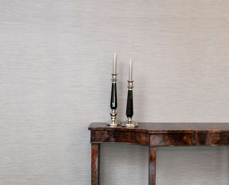 Sideboard in front of a grey wall with candle stick photo