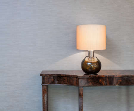 interior wallpaper: Sideboard in front of a grey wall with table lamp