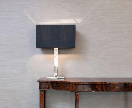 aparador: Aparador em frente a uma parede cinza com candeeiro de mesa