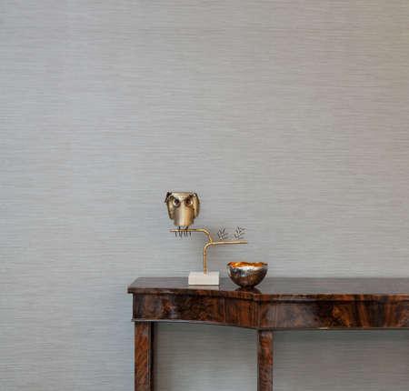 aparador: Aparador na frente de um papel de parede cinza com objetos de arte Imagens