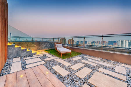 patio chair: Roof terrace with jacuzzi and sun lounger during twilight Stock Photo