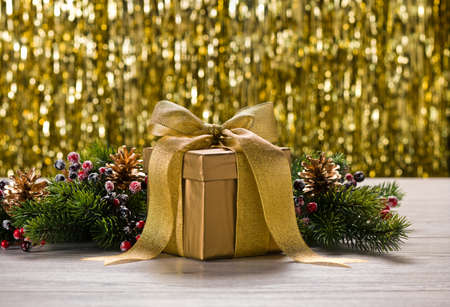 tree branches: Gold present and Christmas tree branches in front of golden background Stock Photo