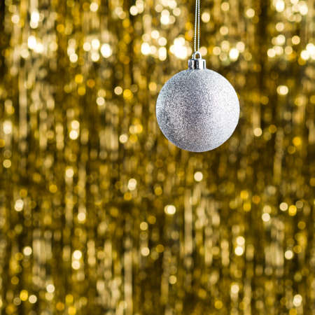 christmas gold: Silver christmas tree ornament over gold glitter background Stock Photo