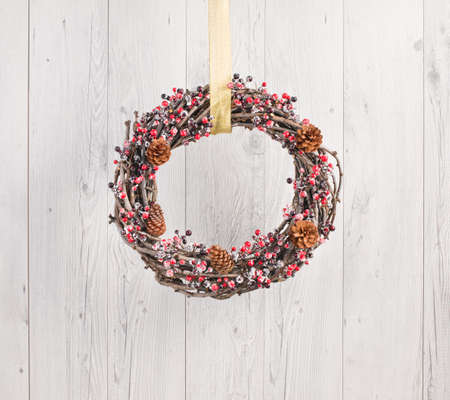 white door: Advents wreath with autumn decoration over a white wooden background
