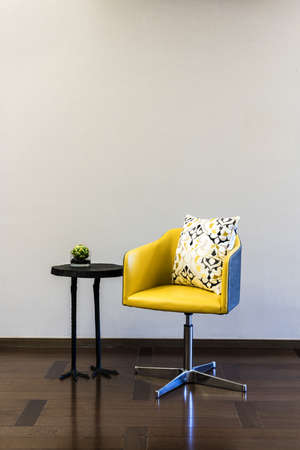 coffee houses: Wooden coffee table yellow chair combination in front of a plain wall