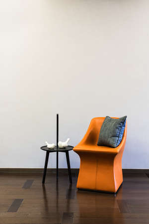 modern chair: Coffee table Orange Leather chair combination in front of a plain wall