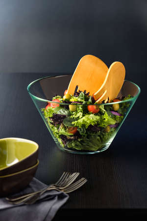 salad bowl: Green salad in glass bowl on a dark table