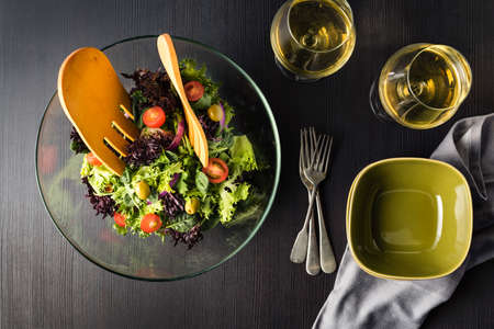 Green salad in glass bowl on a dark table