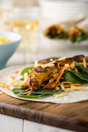 restaurant dining: Fresh healthy chargrilled tandoori chicken wrap with tzatziki, cheese, baby spinach and carrots Stock Photo