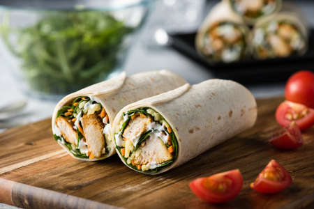 Frische gesunde chargrilled Tandoori Chicken Wrap mit Tzatziki, Käse, Baby-Spinat und Karotten Standard-Bild