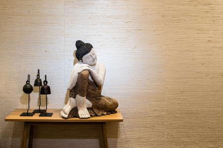 Buddha auf einem Beistelltisch in einem Raum mit schönen Parkettboden
