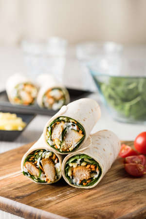 tandoori chicken: Fresh healthy chargrilled tandoori chicken wrap with tzatziki, cheese, baby spinach and carrots Stock Photo