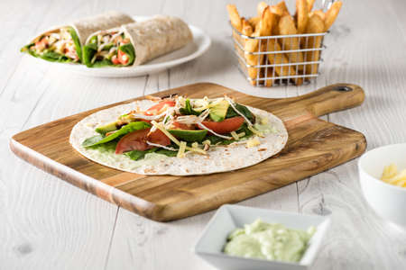 restaurant dining: shredded barbecued chicken wraps with carrot, cheese, avocado and spinach. With French fries on the side.