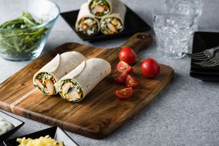 baby spinach: Fresh healthy chargrilled tandoori chicken wrap with tzatziki, cheese, baby spinach and carrots Stock Photo