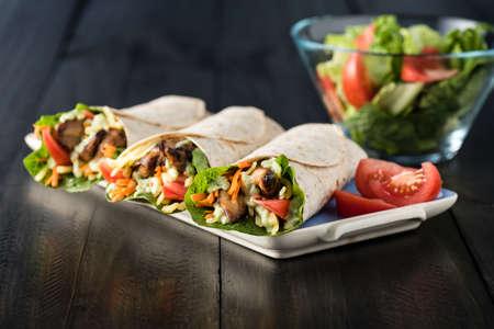 wraps: pollo a la barbacoa con ensalada fresca de tortilla envuelve en el fondo rústico