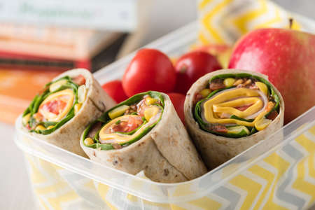 Ham and cheese wraps in lunch box with apple and tomatoes Stock Photo