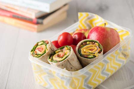 Ham en kaaswraps in lunchdoos met appel en tomaten Stockfoto