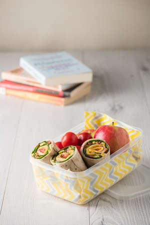 lunch box: Ham and cheese wraps in lunch box with apple and tomatoes Stock Photo