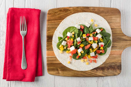 bean curd: vegan tofu wraps with pepper, corn, tomatoes and spinach Stock Photo
