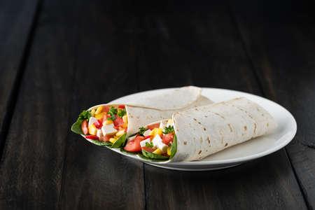 wraps: tofu vegana envuelve con pimiento, maíz, tomates y espinacas Foto de archivo