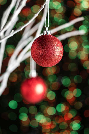 christmas baubles: White twigs with Christmas tree baubles in front of a green red background