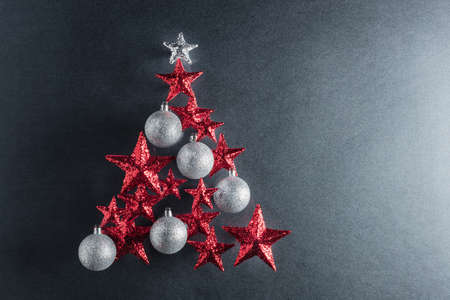 christmas baubles: Christmas tree shape with red stars and silver baubles over color background