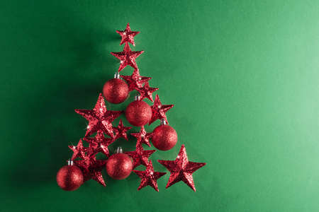 Christmas tree shape with red stars and baubles over color background
