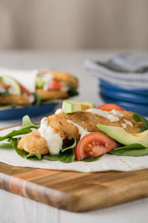 fishfinger: Fish finger wraps with avocado and tomato serves on wooden cheese platter
