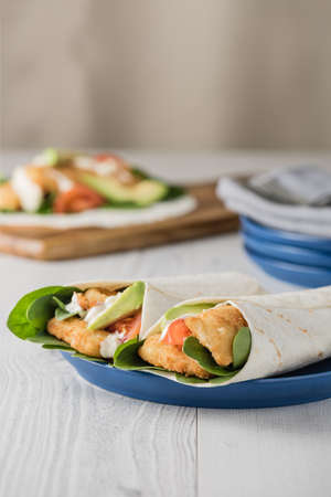 Fish finger wraps with avocado and tomato serves on blue plate Stock Photo