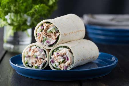 Tonijn burrito's met komkommer rode ui en mayonaise op rustieke achtergrond