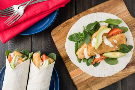 fishfinger: Crumbed fish fillet burrito with avocado and tomato serves on wooden cheese platter with rustic background Stock Photo
